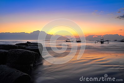 Ocean coast sunrise and blury boats
