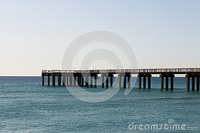 Ocean fishing pier stretchs over calm seas