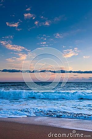 Ocean surf under pink sunset