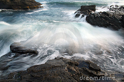 Ocean Wave crashing over multiple rock outcrops