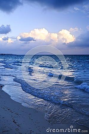 Ocean waves on beach at dusk