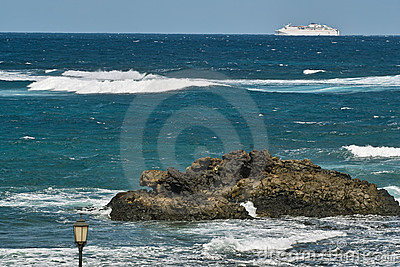 Ocean waves, rocks and white ferryboat