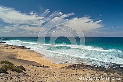 Ocean waves rolls on the footprints on sandy beach