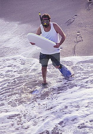 Oddball man with boogie board at beach