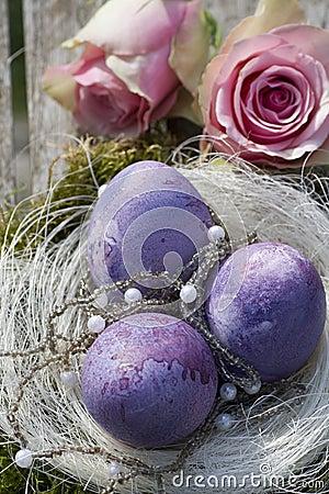 Oeufs de pâques dans le pourpre avec des roses et des perles