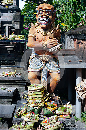 Offerings are made to a traditional balinese statue, Bali, Indon