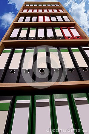 Office cupboard with folders before cloudy sky