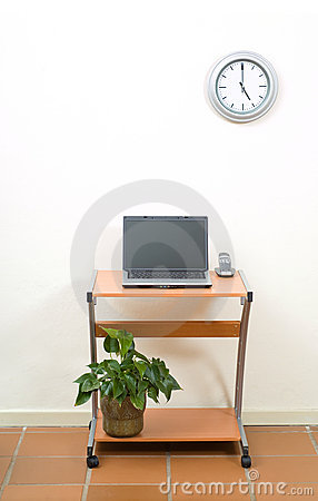 Office desk, laptop and clock