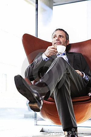 Office manager in red chair enjoying coffee.