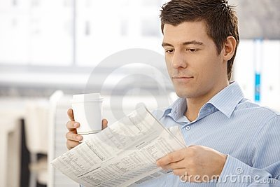 Office worker on break reading papers with coffee