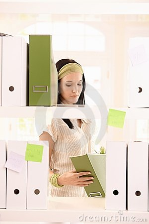Office worker girl packing folders