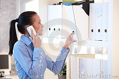 Office worker on mobile phone choosing file folder