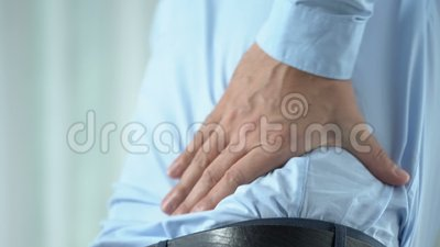 Office worker in 40s feeling sharp back pain, standing up, sedentary lifestyle. Stock footage stock video