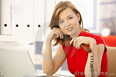 Office worker thinking with phone in hand