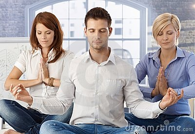 Office workers meditating at work