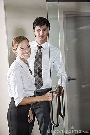 Office workers opening glass door