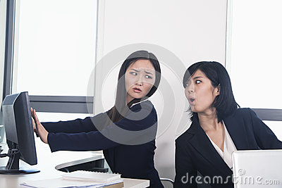Officer worker hiding her computer from coworker