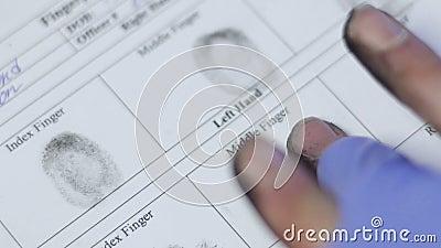 Oficial de policía que toma huellas dactilares del principal sospechoso, marca biométrica del identificador almacen de metraje de vídeo