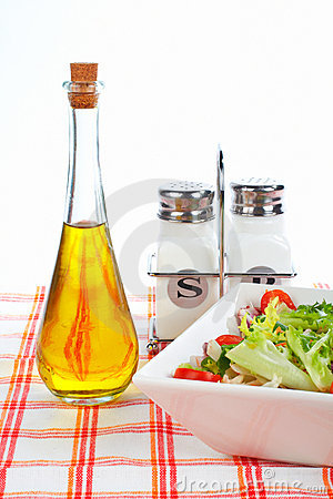 Oil bottle, green salad, salt and pepper