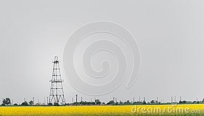 Oil and gas well rig, outlined rural canola field