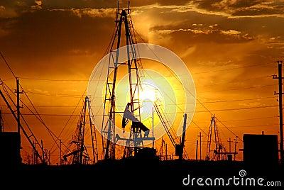 Oil pumps, derricks at sunset