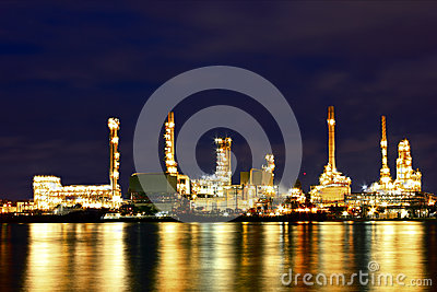 Oil refinery factory with reflection on the river.