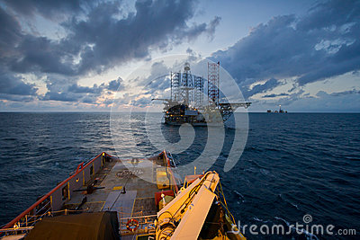 Oil rig platform towed by an offshore vessel during sunset