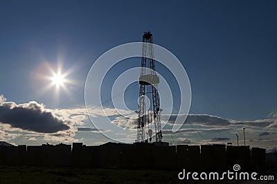 Oil rig silhouette, blue sky.