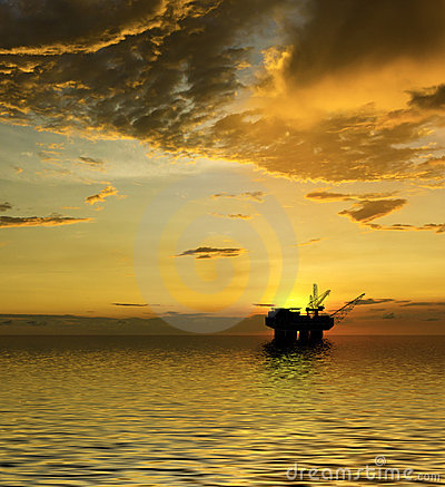 Oil Rig silhouette with majestic ocean and sunset
