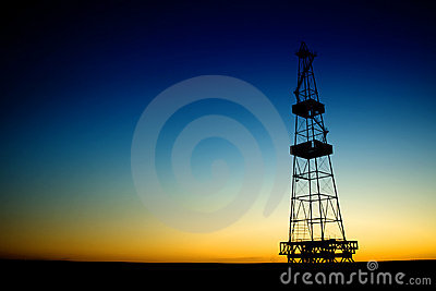 Oil rig silhouette over blue sky