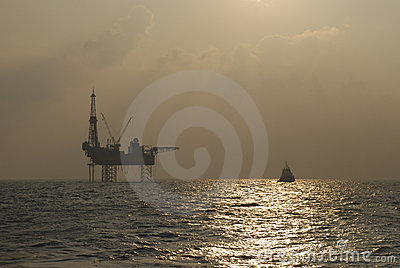 Oil rig with Standby boat in the sunset