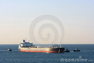 Oil tanker ship at sea with three tug boats