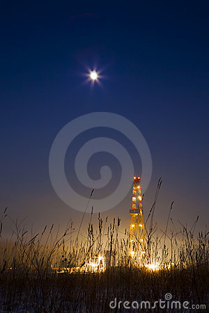Oil well in the snowy landscape lit up at night.