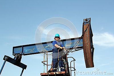 Oil worker standing at pump jack