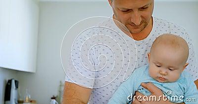 Ojca karmienia mleko jego chłopiec w kuchni 4k zbiory