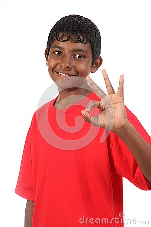 OK signal by young smiling teenager boy in studio