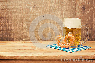Oktoberfest german beer festival background with beer glass and pretzel on wooden table Stock Photo