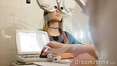 Okulistyka - oko kliniki pojęcie - optometrist i pacjent robi egzaminu wzrokowi nowożytną elektroniczną technologią zdjęcie wideo