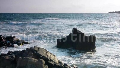 Olas aplastando rocas en la costa metrajes