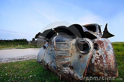Old abandoned car under a blue sky
