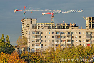 Old apartment house against construction crane