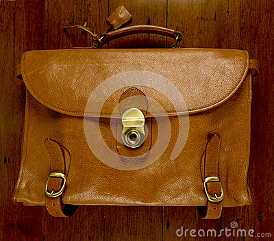 Old battered, leather  briefcase  wood background