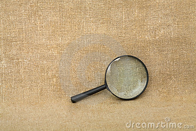 Old black magnifier on drapery background