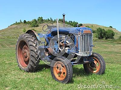 Old blue farm tractor in field.