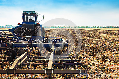 Old blue tractor with a plow. Stock Photo