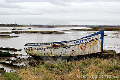 An old boat on the sand on the side of an estuary