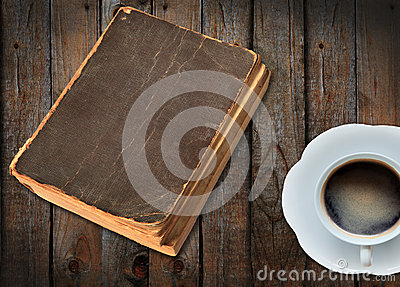 Old book and a cu of coffee on wood