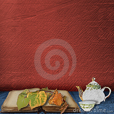 The old book with leaves and  teapot with  cup