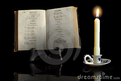 An old book in the light of a candle