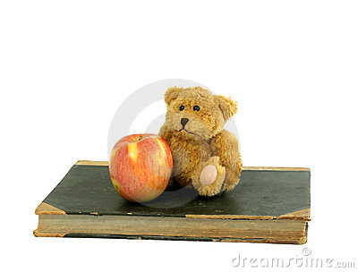 Old book, small bear and apple isolated on white